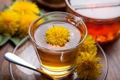 清凉茶和蜂蜜由与黄色开花的蒲公英制成在木桌 库存照片