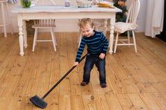 清扫地板的小白肤金发的男孩在厨房里 俏丽的男孩3 yers老帮助做父母与家事 免版税库存图片