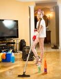 清扫地板的青少年的女孩在室与吸尘器 库存照片
