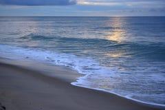 清早在日出的海滩步行与天堂般的天空 免版税库存照片