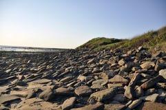 清早多岩石的海滩 图库摄影