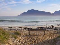 清早山、海滩和一条孤零零长凳在Kommetjie开普敦半岛的在南非 库存图片