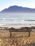 清早山、海滩和一条孤零零长凳在Kommetjie开普敦半岛的在南非 免版税图库摄影