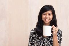 拿着一个白色杯子和微笑对照相机的美丽的亚裔女孩 免版税库存图片