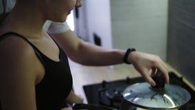 清早拥抱他的有毛巾的爱的人女朋友在头在他们的厨房里有准备的早餐的  股票视频