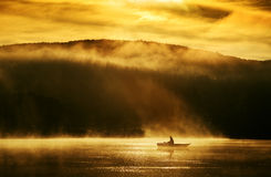清早日出,在湖的划船在阳光下 库存图片