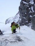 清早朝向一陡峭的雪沟壑和couloir的男性爬山者在他的途中对一个高高山峰顶在Switzerla 库存图片