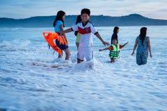 清早,在波浪的家庭游泳在海,越南 免版税库存图片