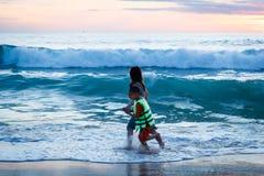 清早,在波浪的家庭游泳在海,越南 免版税库存照片
