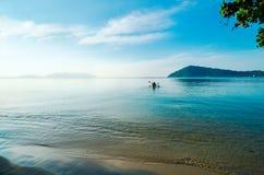 清早,皮船航行到海岛 游人去划皮船在离酸值的附近张,泰国海岸  库存照片