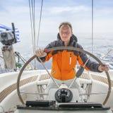 清早年轻人船长一条游艇的舵的在公海 体育运动 免版税图库摄影