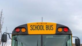 清楚的一黄色学校班车和多云天空的全景正面图有家的在背景中 库存图片
