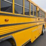 清楚的一黄色学校班车的正方形外视图有一个红色停车牌和尽管信号灯的 免版税库存照片