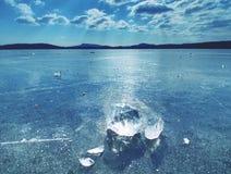 清楚的冰光亮的片断在冻湖的 在太阳光芒的许多反射的里面镇压 库存照片