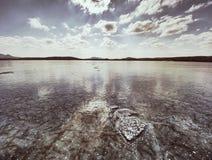 清楚的冰光亮的片断在冻湖的 在太阳光芒的许多反射的里面镇压 免版税库存图片