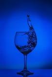 清楚的水吸引抽象飞溅在蓝色颜色的梯度背景反射性表面02上的 图库摄影