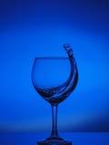 清楚的水吸引抽象飞溅在蓝色颜色的梯度背景反射性表面04上的 免版税库存照片