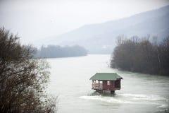 清楚的河(德里纳河在塞尔维亚)有一个岩石的一个小的房子的在山环境美化 免版税库存照片