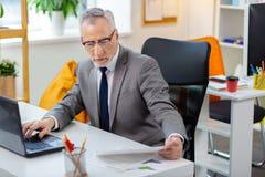清楚的玻璃的繁忙的疲乏的灰发的人读报纸和检查膝上型计算机的 图库摄影