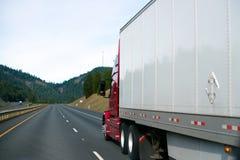 清楚的红色大半船具卡车在perspectiv的白色干燥van trailer 库存照片