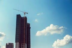 清楚的蓝天的背景的未完成的摩天大楼 免版税库存图片