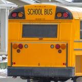 清楚的运行在有新鲜的雪的一条路的一黄色学校班车的正方形背面图在冬天 库存图片