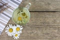 清楚的透明杯子在葡萄酒木背景的甘菊茶用干草本、雏菊花和拷贝空间 免版税图库摄影