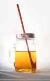 清楚的金属螺盖玻璃瓶与秸杆和盒盖的苹果汁 免版税库存照片
