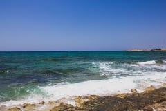 清楚的陆间海的美丽的景色有白色泡沫波浪的在岩石岸 在塞浦路斯的晴朗的海景 免版税库存图片