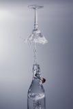 清楚的水倾吐在瓶飞溅外面入与灰色后面的玻璃 免版税库存图片