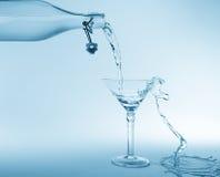 清楚的水倾吐在瓶飞溅外面入玻璃并且溢出与 免版税库存照片