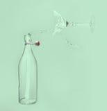 清楚的水倾吐水平在瓶飞溅外面入玻璃与 免版税库存照片