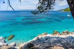 清楚的绿松石海水、树、小船和石头 希腊 免版税库存图片