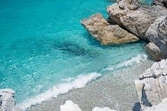 清楚的绿松石海水、石头和波浪 希腊 免版税库存照片
