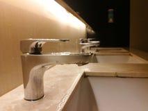 清洁卫生间水槽在公开休息室 免版税库存照片