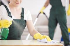 清洁女工喷洒的桌 免版税图库摄影