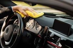 清洁汽车 有microfiber布料清洁汽车内部的手 免版税库存照片