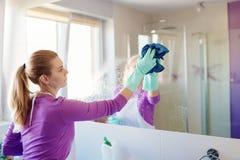 清洁镜子的年轻美丽的妇女在卫生间里 免版税图库摄影