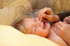 清洁babys鼻子 免版税图库摄影