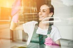清洗和抹窗口的美丽的微笑的年轻女人与浪花瓶 免版税库存图片
