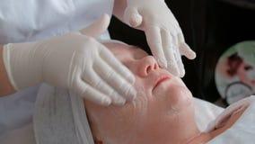 清洗在女孩的脖子、面颊和前额的皮肤做法与在整容术的闭合的眼睛 股票视频