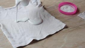 清洗在小孩衣服的污点的母亲从糖果在去污剂和洗衣粉,特写镜头帮助下 股票视频
