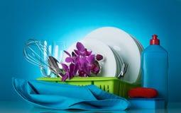 清洗在烘干机、洗涤剂、海绵和餐巾的盘,在蓝色 图库摄影