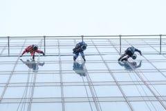 清洗在高层建筑物的三名工作者窗口服务 免版税库存图片