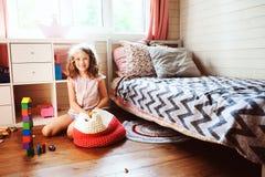 清洗她的室的儿童女孩和组织木玩具入被编织的存贮袋子 免版税库存图片