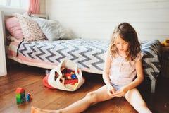 清洗她的室的儿童女孩和组织木玩具入被编织的存贮袋子 免版税库存照片