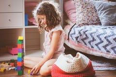 清洗她的室的儿童女孩和组织木玩具入被编织的存贮袋子 库存照片