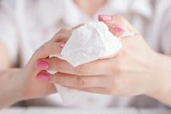 清洗她的手的妇女通过使用白色薄纸 免版税库存照片