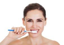 清洗她的牙的微笑的妇女 免版税库存照片