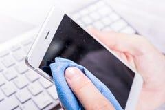 清洗尘土、土和指纹的智能手机屏幕商人与清洁抹在他的书桌 免版税库存照片